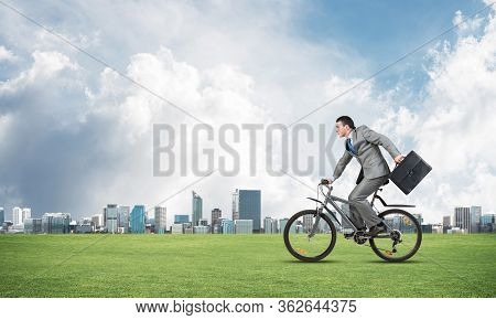 Young Man Riding Bicycle On Green Grass. Businessman On Bike Hurry To Somewhere. Corporate Employee