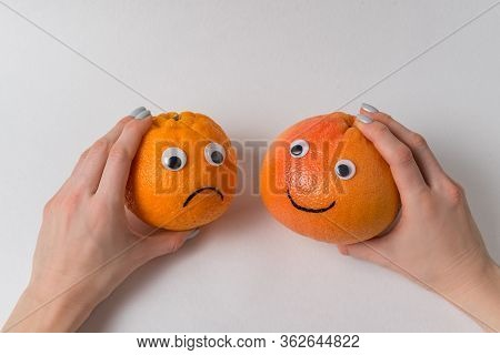 Hands Holding Orange And Grapefruit With Funny Faces On White Background. Pessimist And Optimist Con