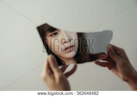 Broken Mirror Reflect The Face Of Thai Girl.