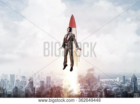 Businessman In Suit And Aviator Hat Flying On Rocket. Superhero Businessman Flying With Jetpack Rock