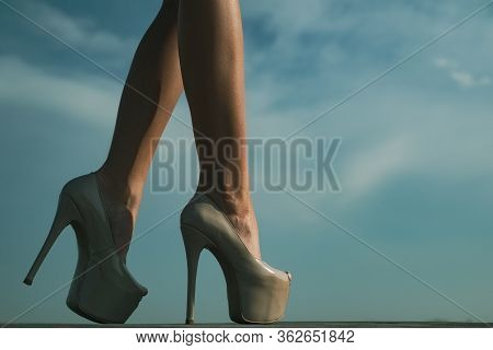 Close-up Of Young Womans Legs In High Heeled Shoes. Beautiful Female Legs With Heels On Sky Backgrou