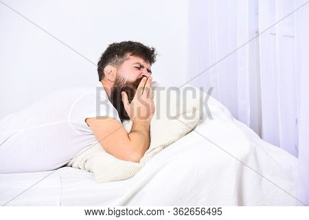 Man In Shirt Yawning While Laying On Bed, White Wall And Curtain On Background. Sleepyhead Concept.