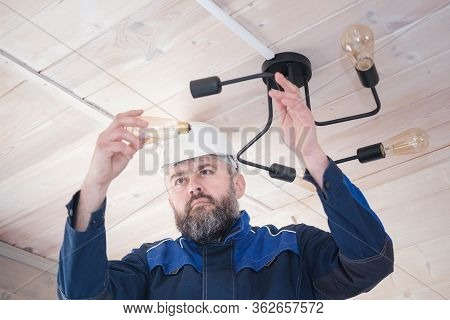 A Male Electrician Performs In A White Hard Hat And With A Beard Performs The Replacement Of A Light
