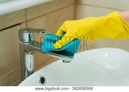 Someone Is Washing A Sink With Sponge. Someone Is Washing A Sink In Yellow Gloves.