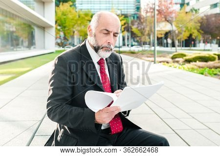 Concentrated Businessman Reading Reports Outdoors. Focused Bearded Mature Man Sitting On Street With