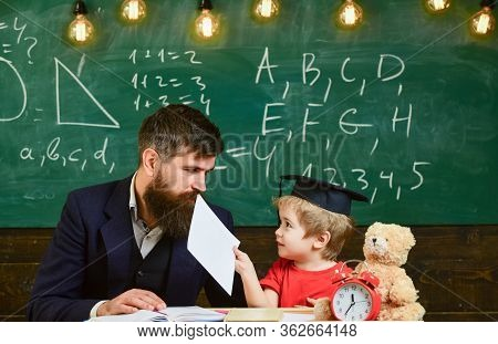 Little Boy Shows His Copybook With Paintings. Teacher And Pupil In Mortarboard, Chalkboard On Backgr