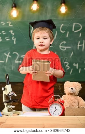 Boy In Graduation Cap With Book Standing Near Green Chalkboard. First Former Interested In Studying,