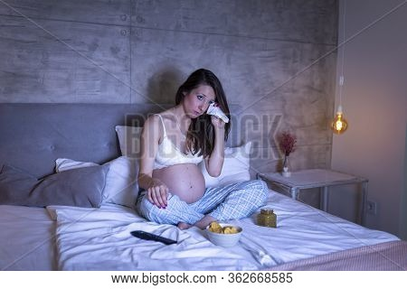 Pregnant Woman Wearing Pajamas Sitting On Bed And Crying While Watching A Sad Movie On Tv, Wiping Te