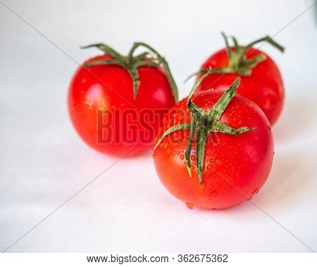 Red Tomatoes With Sepals On A White Background. Three Tomatoes