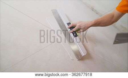 Plaster On A Wall. Worker Plastering The Walls With A Spatula.