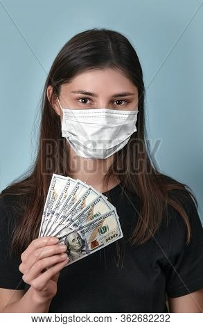 Woman In Face Mask Get Allowance During Coronavirus Covid 19 Looking In Camera. Girl Is Holding Doll