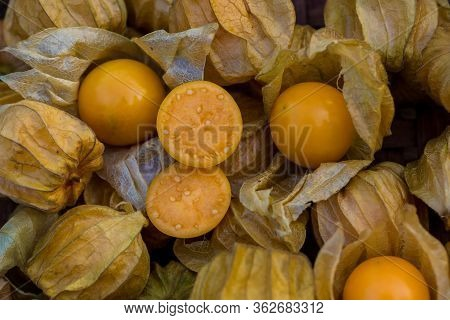 Pile Of Cape Gooseberry On Sale In The Market. Physalis Fruits  On A Black Basket Background. Gape G