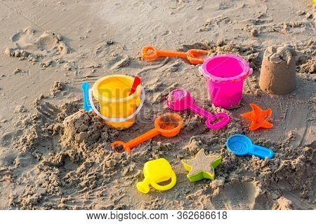 Plastic Sandbox Toys On The Sand. Kids Toys On Tropical Sand Beach. Plastic Shovel And Sea Animal Mo