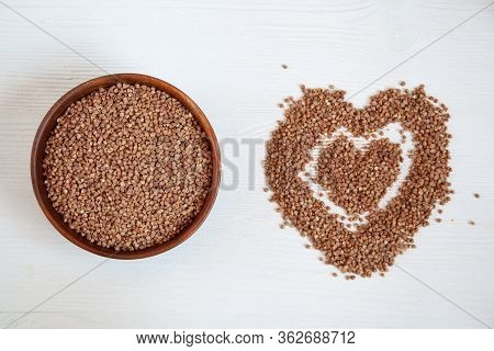 Buckwheat In A Wooden Bowl On A White Table And Next To A Heart Of Buckwheat.