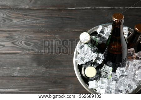 Metal Bucket With Bottles Of Beer And Ice Cubes On Black Wooden Background, Top View. Space For Text