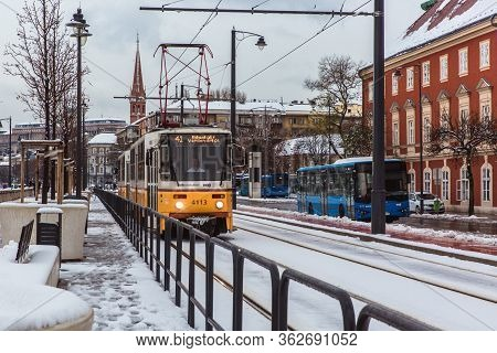 Budapest, Hungary - December 02, 2019: Yellow Tram And Tramlines In Budapest At Winter With Snow Nea