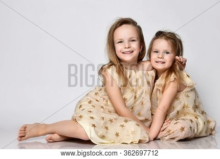 Two Small Beautiful Smiling Girls Sisters In Same Dresses With Stars Sitting On Floor And Cuddling O