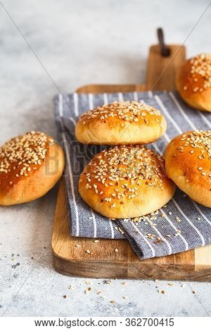 Bun Buns With Sesame Seeds On A Wooden Board.