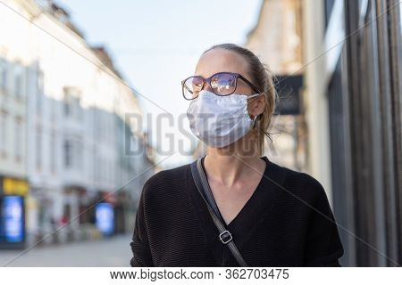Covid-19 Pandemic Coronavirus. Young Girl In City Street Wearing Face Mask Protective For Spreading