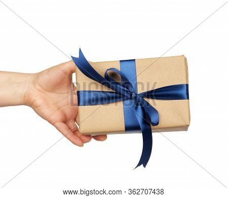 Hand Hold A Wrapped Gift In Brown Craft Paper With Tied Silk Blue Bows, Subject Is Isolated On A Whi