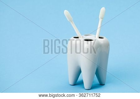 Toothbrush Stand Shaped Like Primary Molar Tooth With Two Toothbrushes Close Up Isolated On Blue Bac