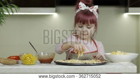 Cooking Homemade Pizza. Little Child Girl Adding Grated Cheese To Dough With Tomato Sauce, Smiles Ha
