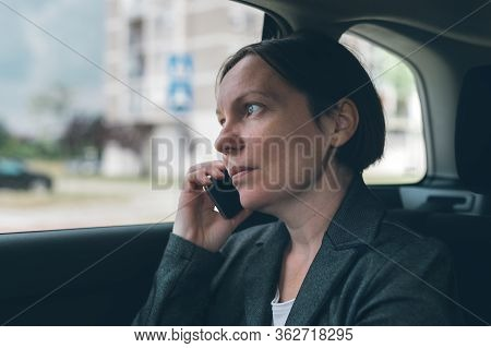 Disappointed Businesswoman Talking On Mobile Phone On Car Back Seat, Business On The Move Concept. E