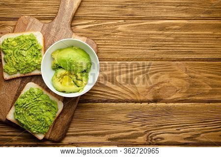 Homemade Avocado Toasts And Smashed Fresh Ripe Avocados In Bowl On Cutting Board On Wooden Rustic Br