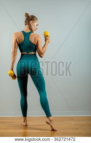 Fit Woman Lifting Weights. Beautiful Fitness Girl On A Gray Background Posing With Dumbbells On A Gr