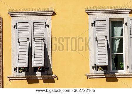 Two Windows With Grey Wooden Shutters With Spike Steel Sticks To Prevent Birds From Stopping, Especi