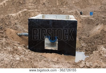 Valve Pit For Underground Piping Networks On Construction Site. Concrete Manhole Rings And Valve Cha