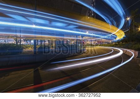Light Trails Of Car On Road In Downtown At Night. Traffic Background