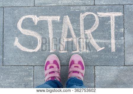 Start Concept. Child Girl Legs Standing On Sidewalk In Front Of Hand Written Chalk Start Word. Back