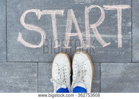 Start Concept. Teenager Girl Standing Legs On Sidewalk In Front Of Word Hand Written Chalk Start. Ba