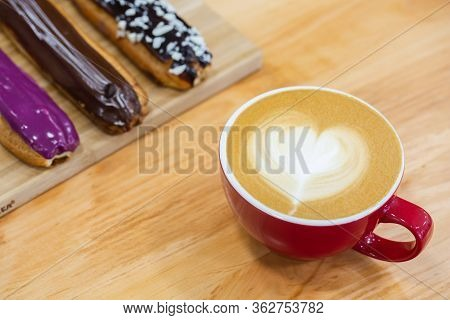 Red Cup Of Hot Art Cappuccino With A Heart On A Foam. Assorted Eclairs On The Table.