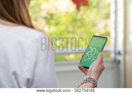 20% Off Sale. Internet Marketing. Young Woman Holding A Smartphone With A 20% Discount Advertising O