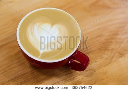 Red Cup Of Hot Art Cappuccino With A Heart On A Foam.