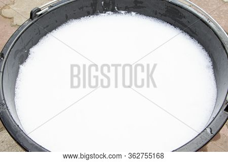 Soapy Water In A Black Bucket. Suds And Soapy Water. A Bucket Of Soapy Water