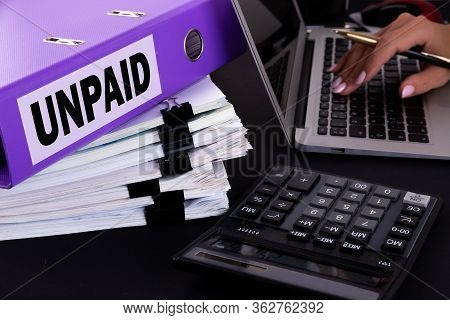Text, Word Unpaid Is Written On A Folder Lying On Documents On An Office Desk With A Laptop And A Ca