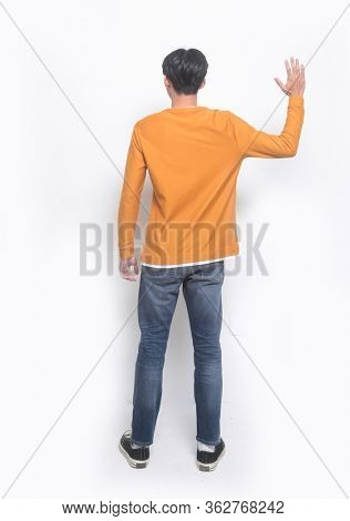 Back view full body,young man isolated on white background wearing brown clothes and blue jeans with standing doing stop sing with palm of the hand.