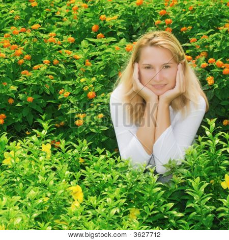 Young Woman Sitting In Flowers