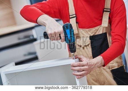 kitchen installation. Worker assembling furniture