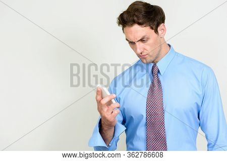 Portrait Of Stressed Young Businessman Looking Angry While Using Phone