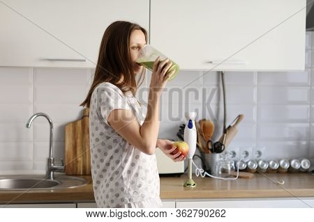 Eautiful Girl Drinks Freshly Prepared Smoothie In Kitchen. Smoothies Freshly Made From Assorted Vege