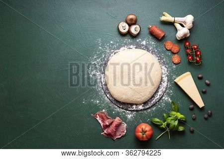 Preparing Pizza Context With Pizza Dough And Ingredients On A Green Background. Top View Of Pizza In