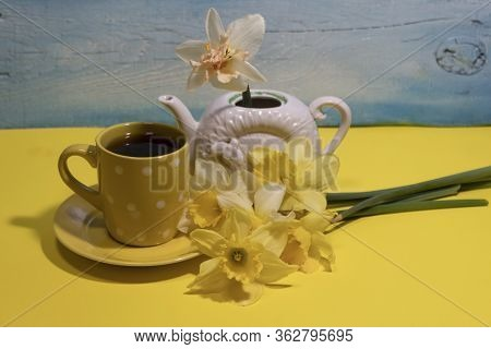 Next To A Cup Of Tea Is A Bouquet Of Daffodils. There Is One White Daffodil In The Teapot.