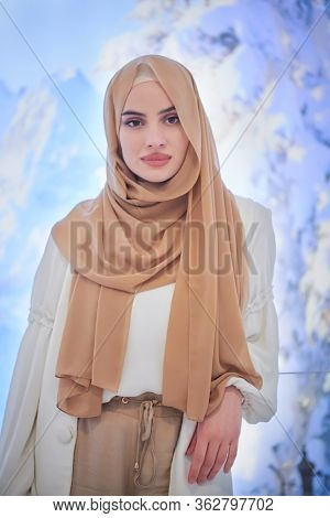 portrait of beautiful muslim woman in fashionable dress with hijab isolated on modern winter mountains background representing modern islam fashion and ramadan kareem concept