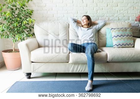 Full Length View Of A Caucasian Brunette Woman In Her 40s Sitting In A Couch And Relaxing At Home In
