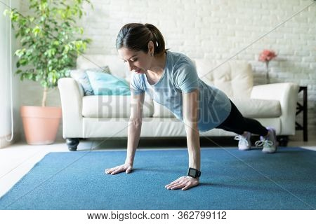 Pretty Woman In Her 40s Wearing A Smartwatch While Exercising At Home And Doing Some Push Ups