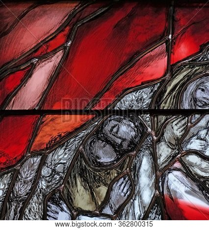 PIFLAS, GERMANY - JUNE 07, 2015: God bears the guilt of all mankind, takes hold of sinners and saves them from death, detail of stained glass window by Sieger Koder in St. John church in Piflas